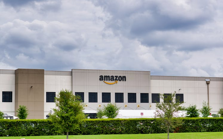 Image shows low-rise white Amazon building with greenery in the foreground against a light cloudy sky
