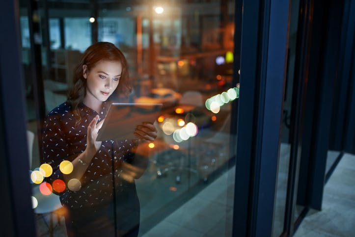 Young woman faces out of office window which reflects coloured lights from outside while using tablet device