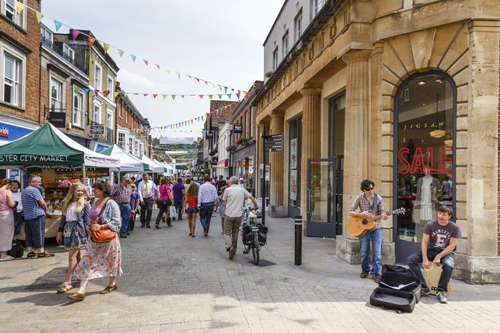 Image shows quaint UK high street with shoppers and buskers