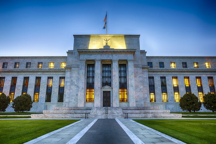 Image shows the front of the Federal Reserve buiding at dusk with lights showing through the windows