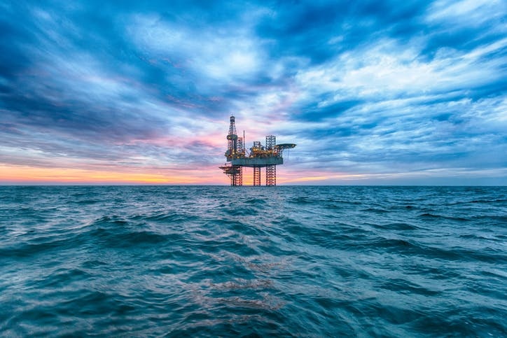 Offshore oil rig on the horizon standing in a green sea with blue cloudy sky ending in a pink sunset