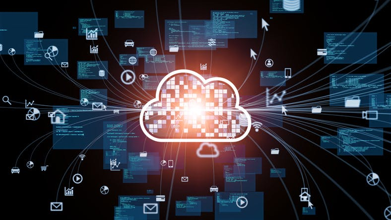 Image shows bright flourescent cloud computing icon against a dark background of tech imagery