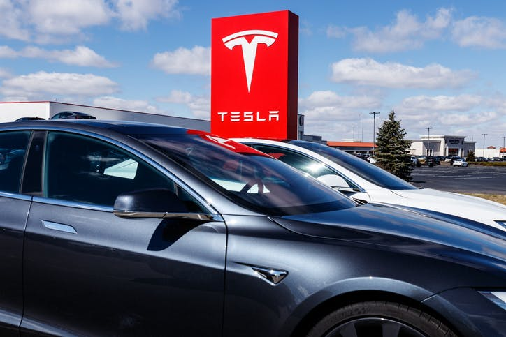 Two parked Tesla cars side by side, dark grey nearest with silver one behind. Large red Tesla sign behind against a light blue sky with feint clouds