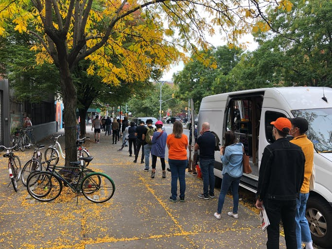 Image shows a queue of people socially distancing as they wait to vote on an Autumn day with white van on right and bicycles on left