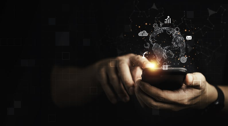 A pair of hands tap on a mobile phone. Light comes out of a fingertip against a dark background