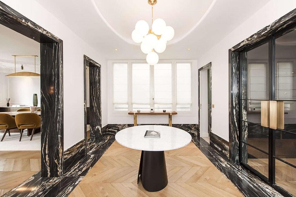 vestibule avec déco haut de gamme mêlant marbre, parquet à chevrons et accessoires design