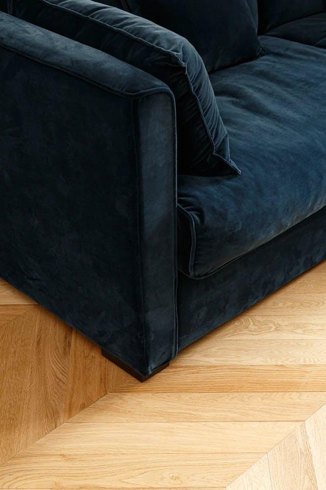 Canapé en velours bleu nuit et parquet stratifié