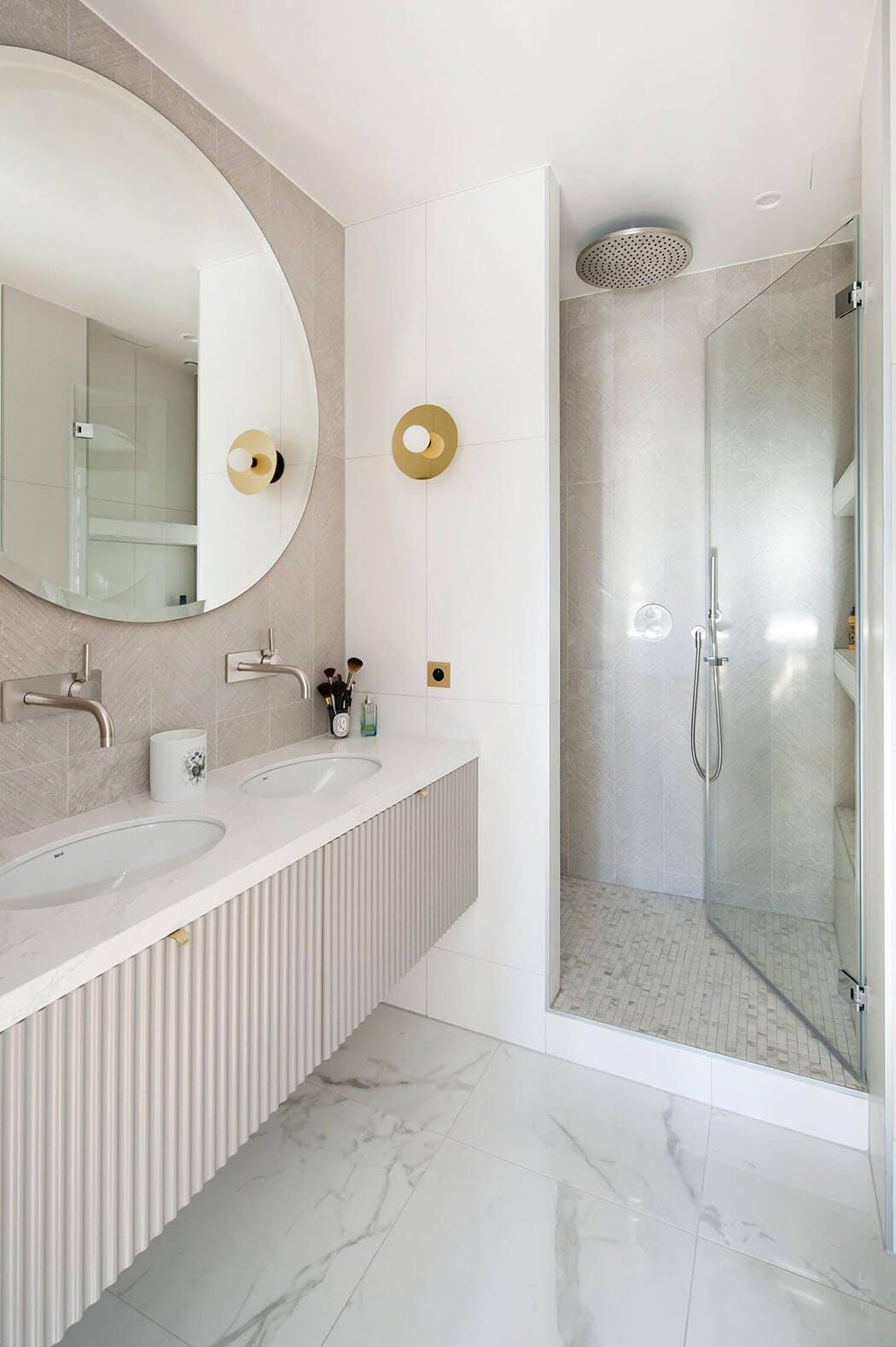 salle de bain de luxe avec double vasque, marbre au sol, et douche à l'italienne avec sol mosaïques