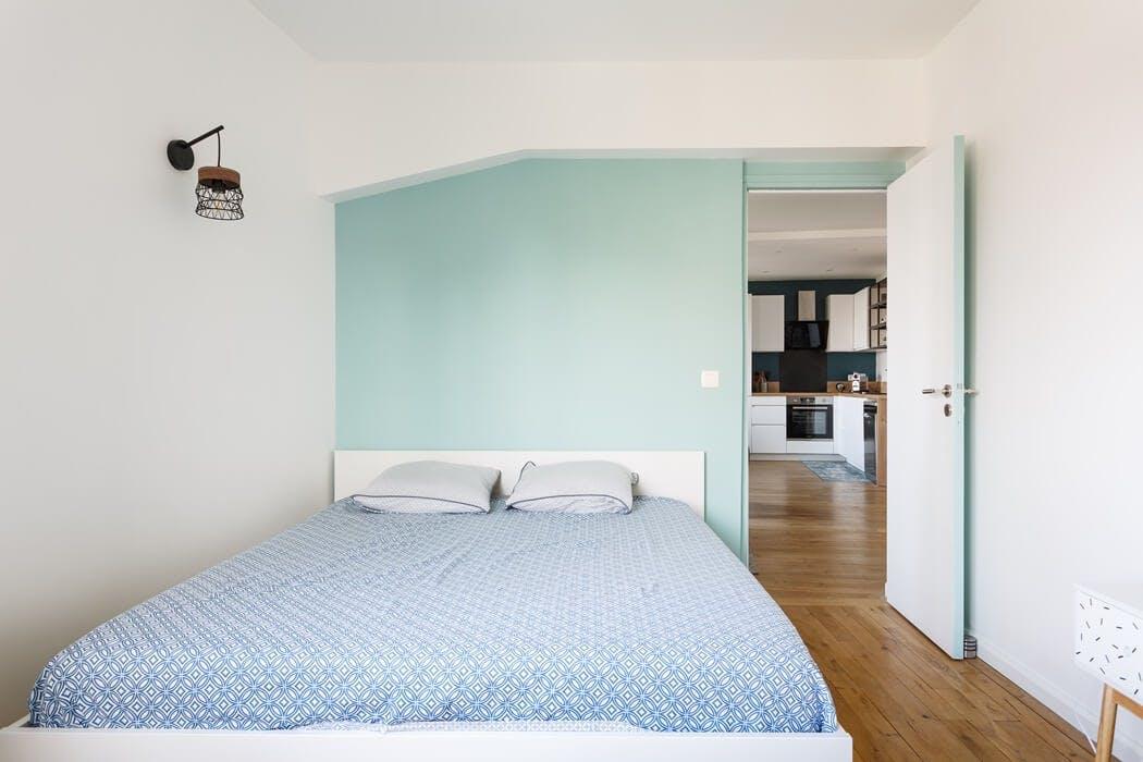 chambre parentale avec un mur vert pastel pour créer une ambiance apaisante
