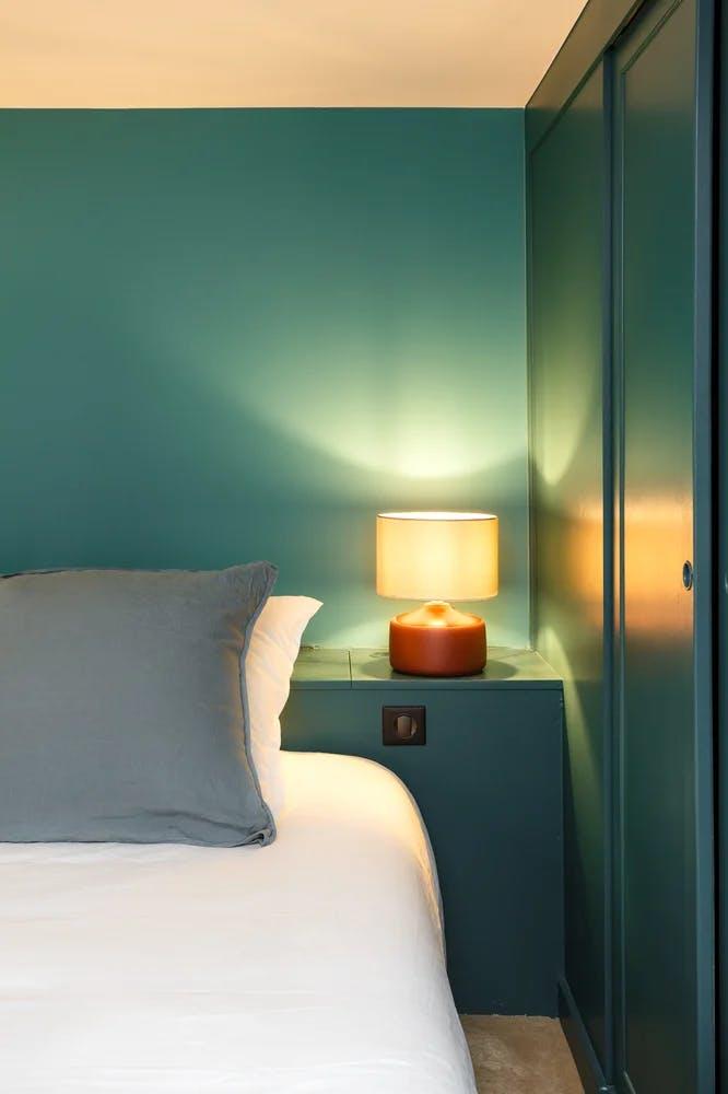 Coin chambre à coucher lampe et mur bleu canard