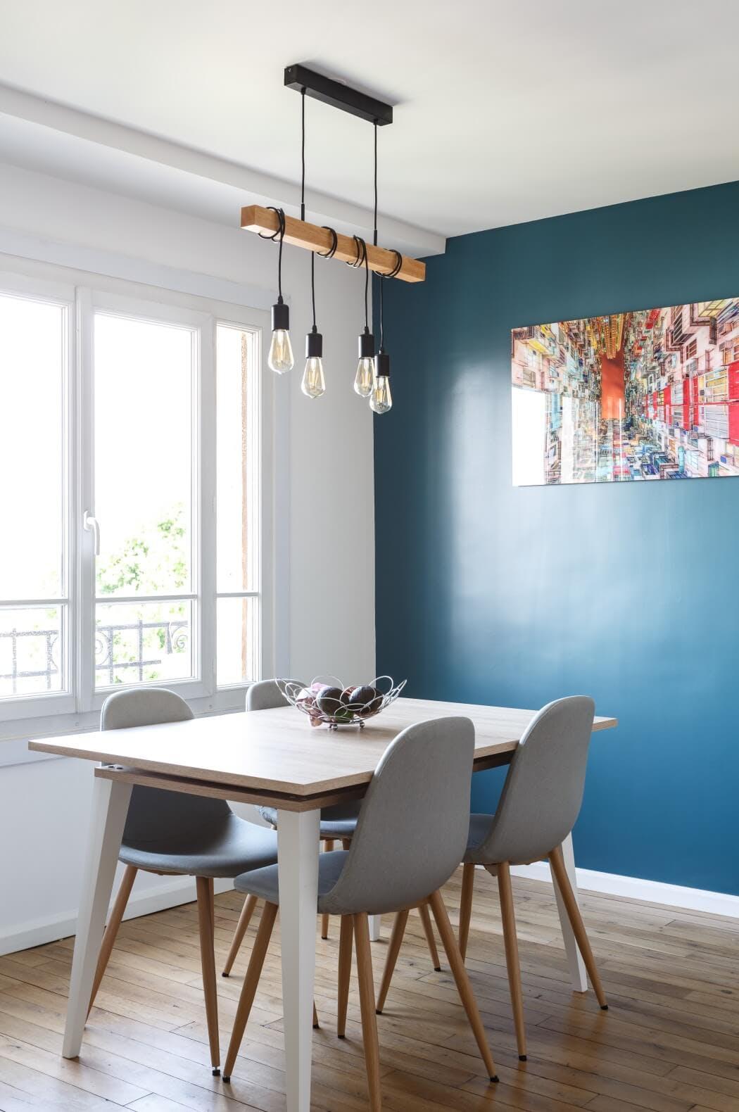 L'espace repas au style scandinave, avec un pan de mur couleur vert canard et un joli parquet