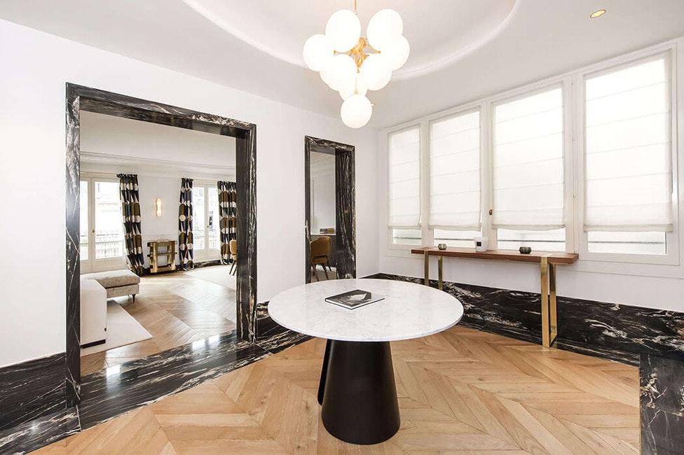 Vue sur le salon depuis le vestibule de cet appartement luxueux en marbre et parquet massif