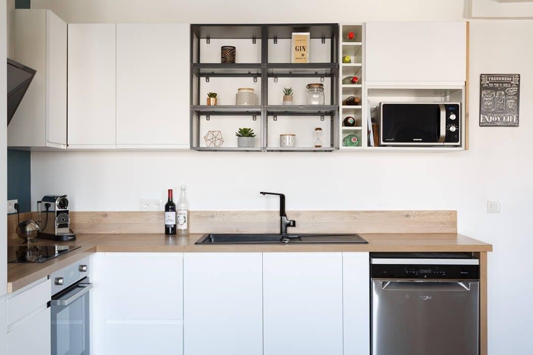 Zoom sur la cuisine blanche, son plan de travail en bois massif, et ses nombreux rangements