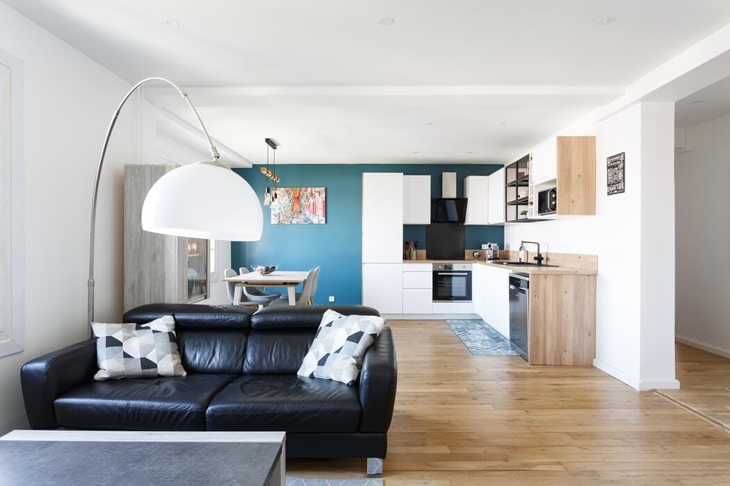Cuisine ouverte sur le salon avec un mur vert canard et un joli parquet massif
