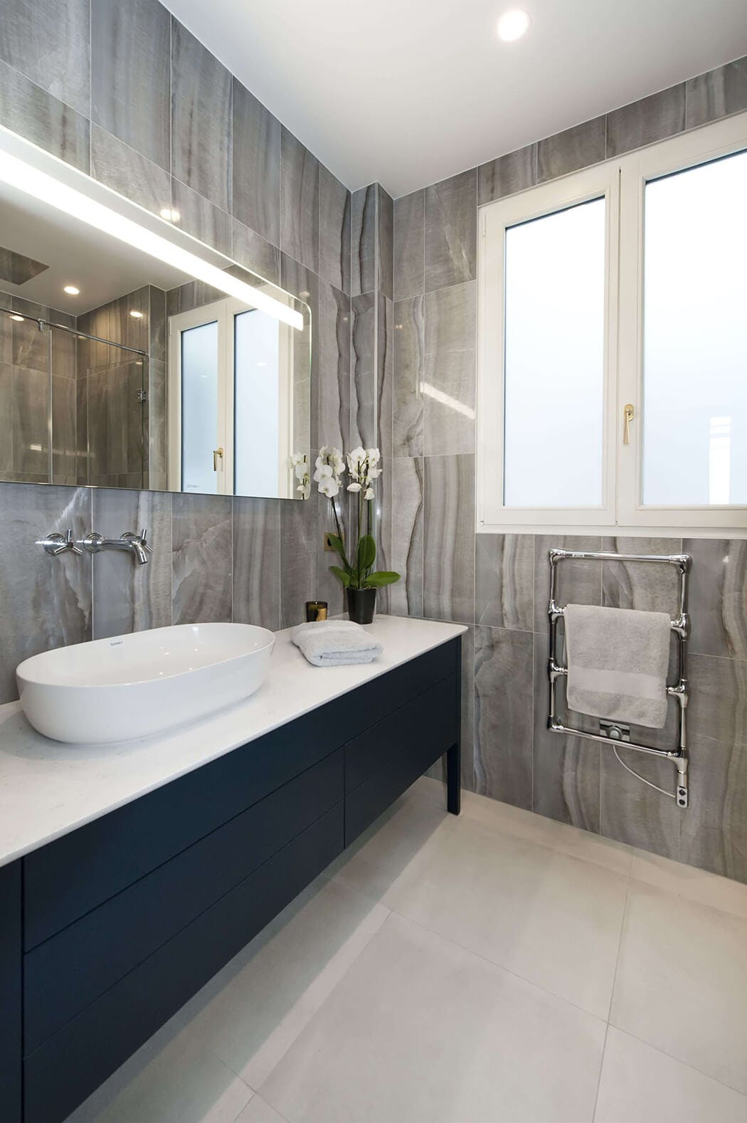 salle de bain de luxe entièrement rénovée avec grand miroir, marbre aux murs et meuble sous vasque anthracite