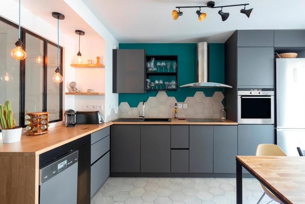 Installation de meubles de cuisine haut de gamme gris surmontés d'un plan de travail en bois massif