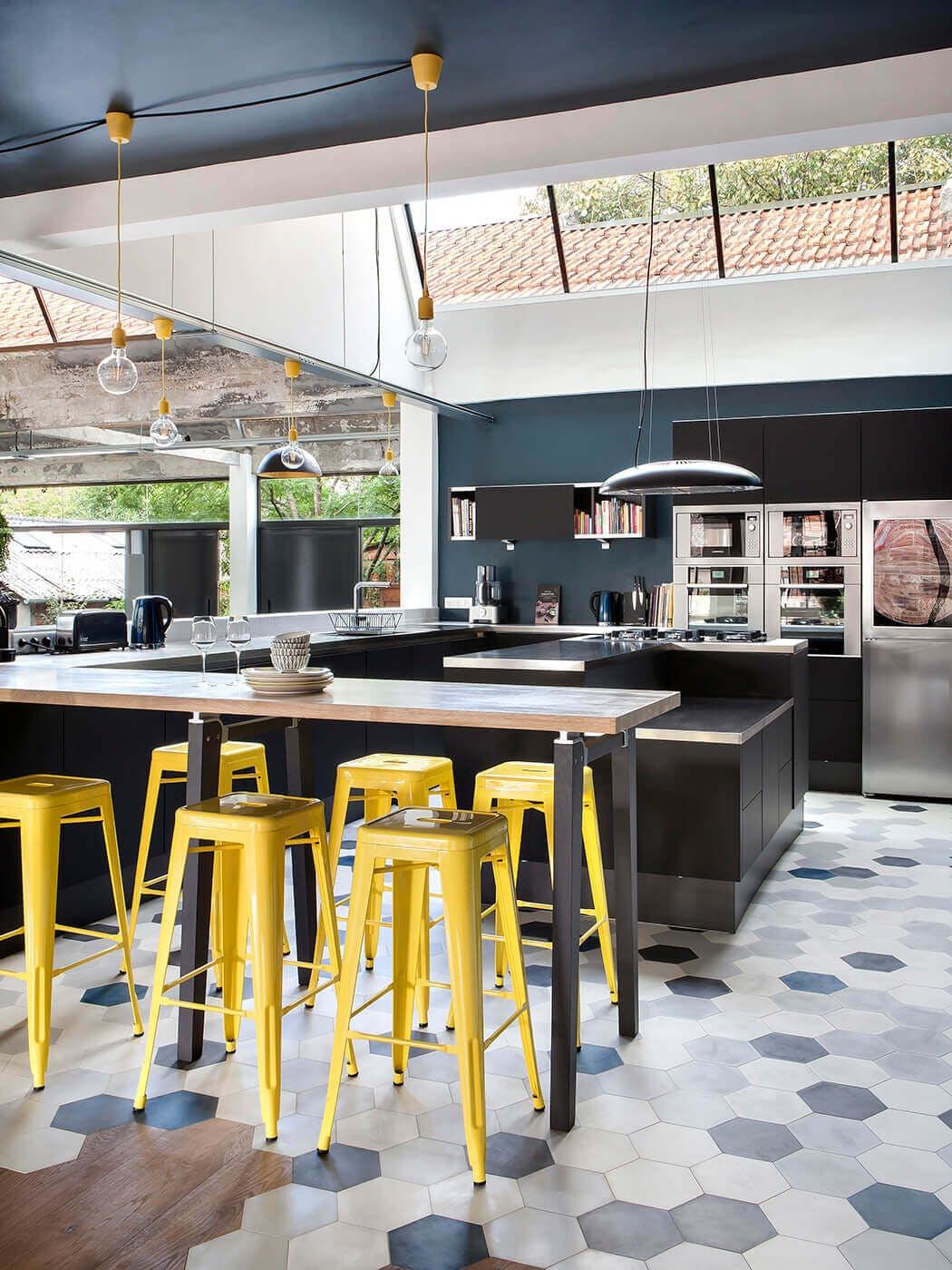 Dans la cuisine luxueuse de ce loft, les éléments sont très épurés et le sol mêle carrelage et parquet