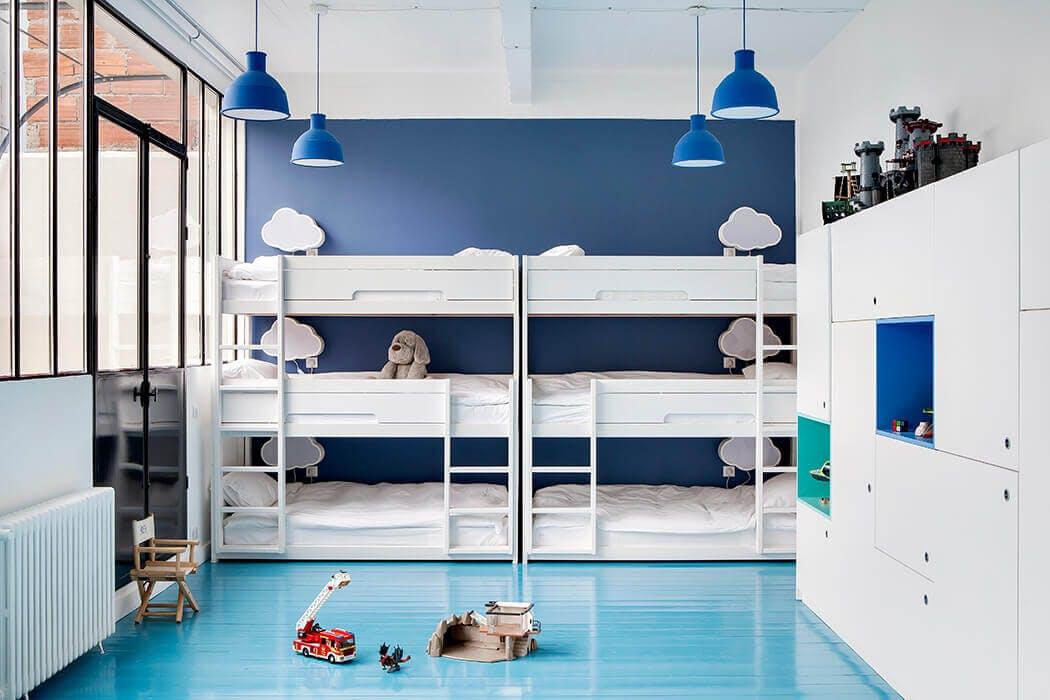 Une chambre d'enfants très épurée avec lits superposés, rangements sur-mesure et verrière.
