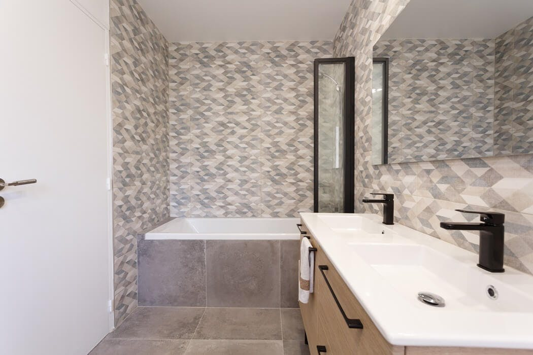 Salle de bain au style dynamisant, grâce à un carrelage mural aux motifs géométriques
