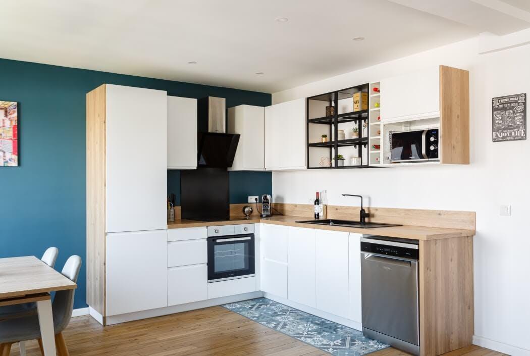 Vue sur la cuisine en L, en partie recouverte de bois massif, et devant laquelle quelque carreaux de ciment ont été posés pour faciliter l'entretien du sol