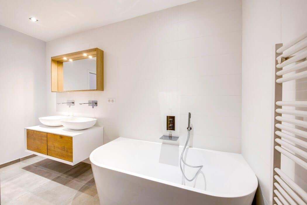 Salle de bain blanche avec double vasque et baignoire aux angles arrondis