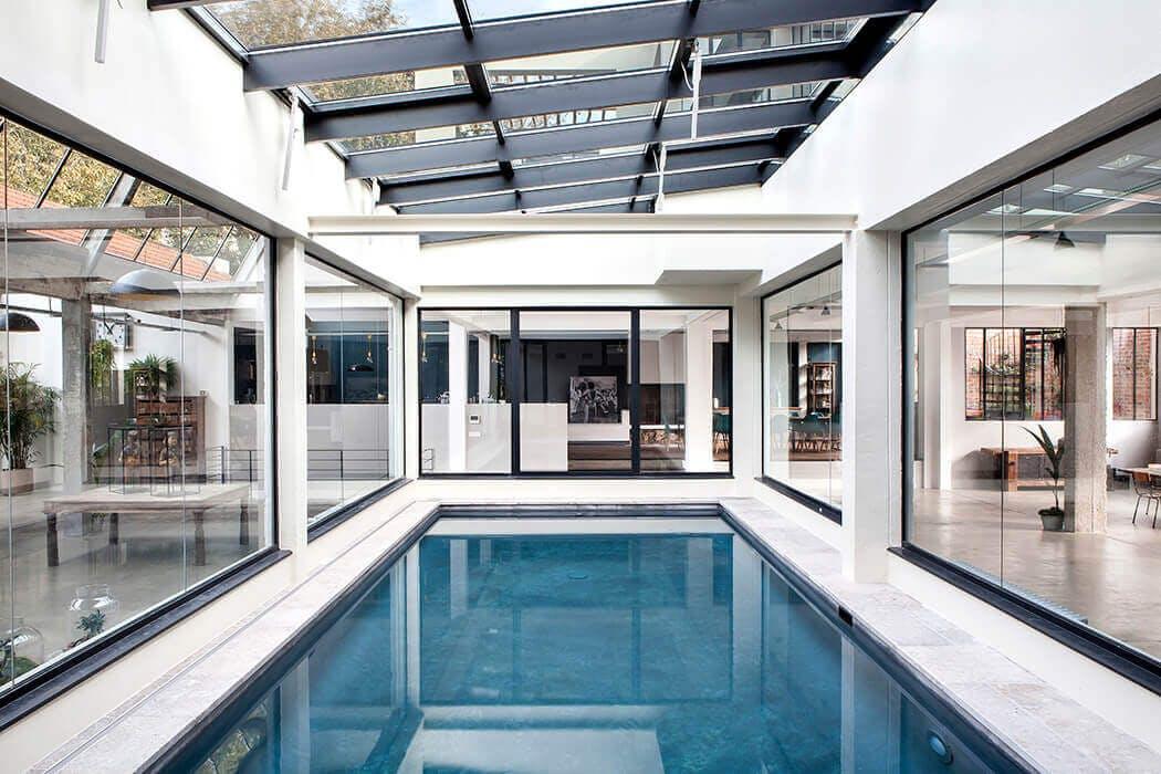 piscine intérieure de luxe baignée de lumière au centre de cette prestigieuse demeure