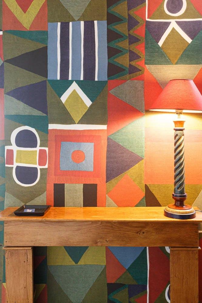 Mur multicolore, meuble en bois et lampe de table - appartement de 65 m² à Paris