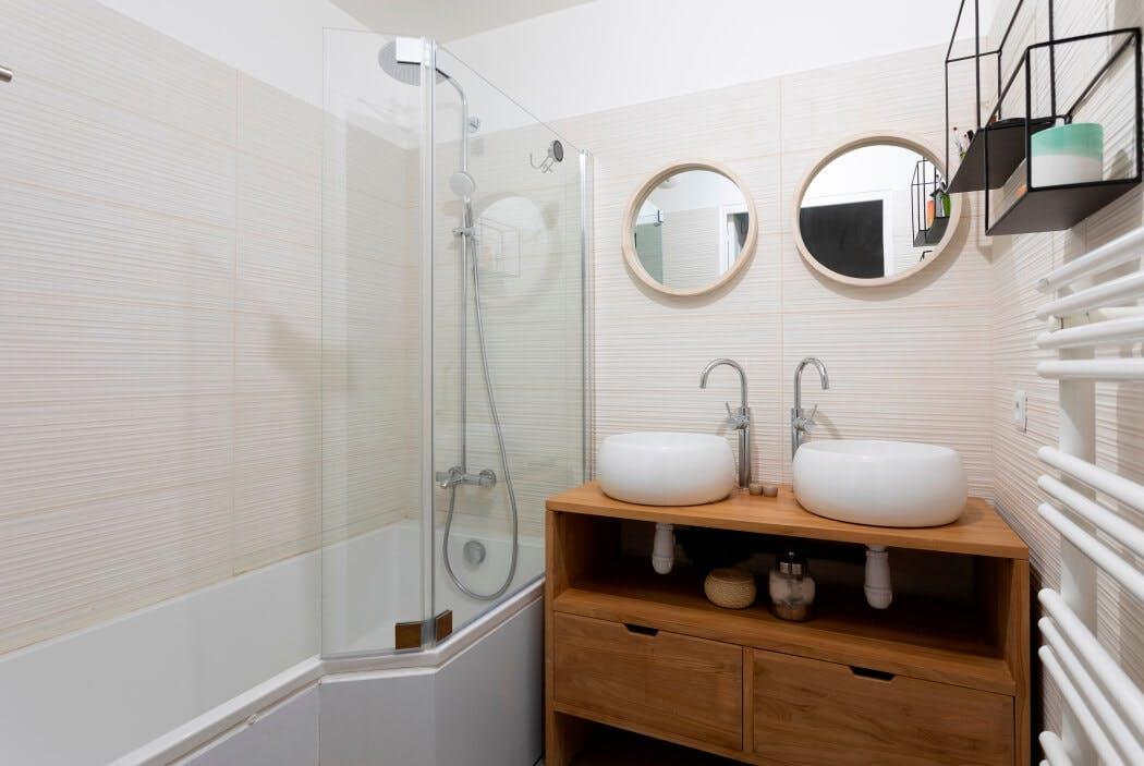 Rénovation de salle de bain avec baignoire douche et meuble sous vasque en bois massif