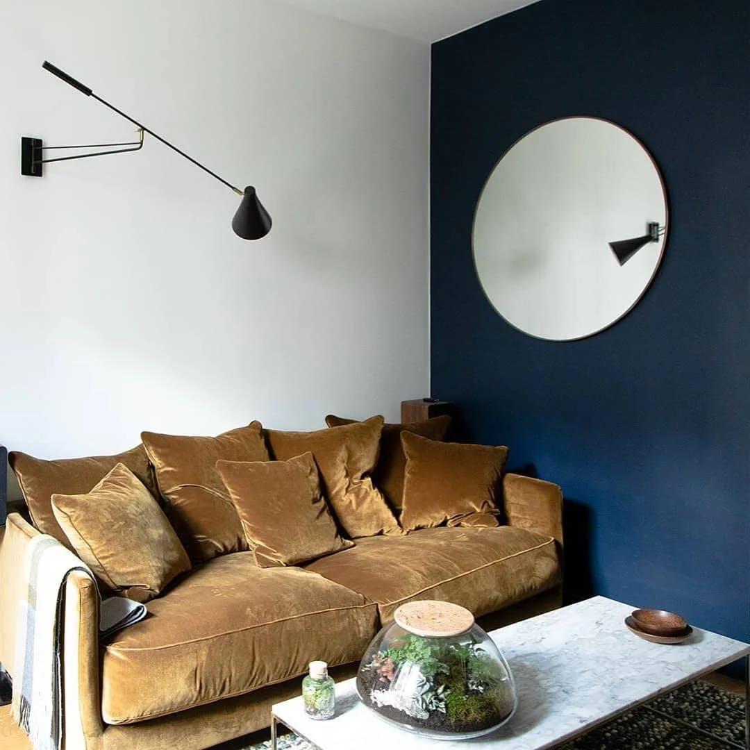 Canapé en velours, table basse en marbre et murs de couleurs différentes