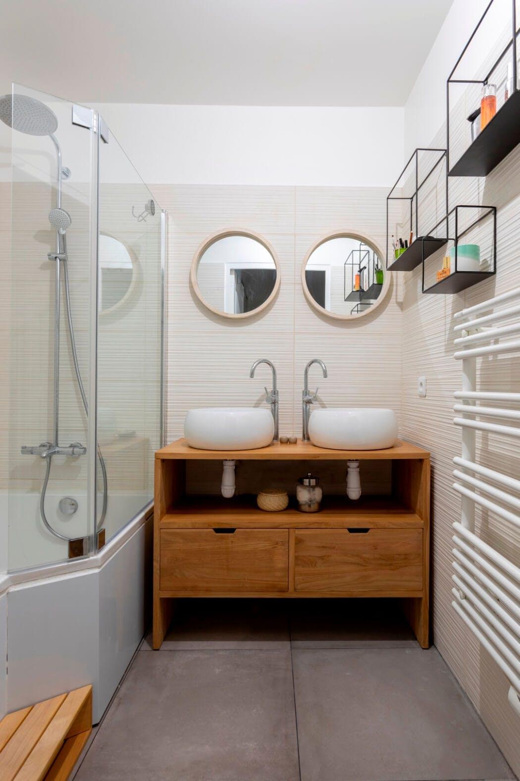 Rénovation de salle de bain dans un style naturel avec dalles de béton au sol et meuble sous vasque en bois