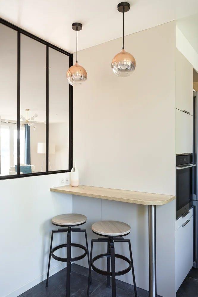 Petite table comptoir avec 2 tabourets à côté d'une verrière et lampes suspendues