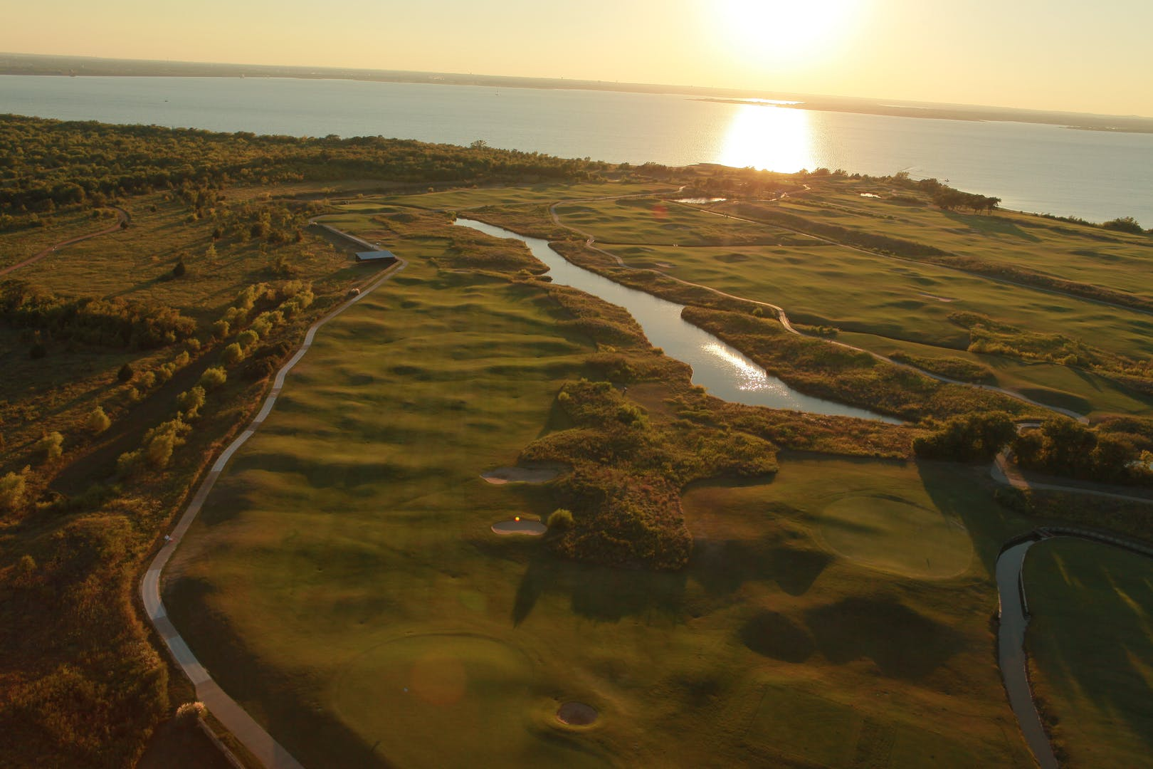 Aerial view of the golf course while the sun sets over Lake Lewisville.