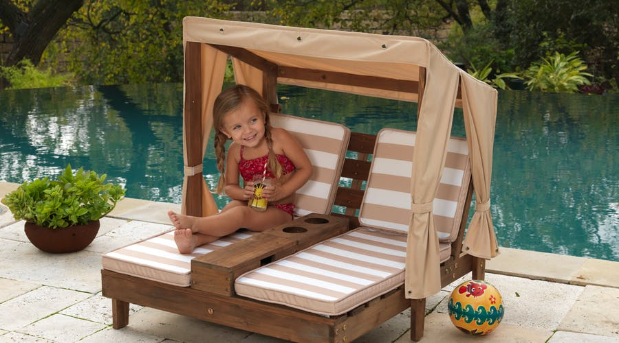 A young girl relaxing on a child sized sun lounger.