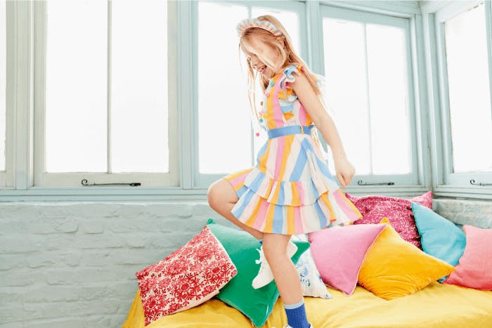 A young girl in a colourful dress, dancing on a bed.