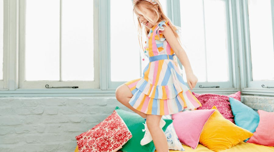 A young girl in a colourful dress playing on a bed.