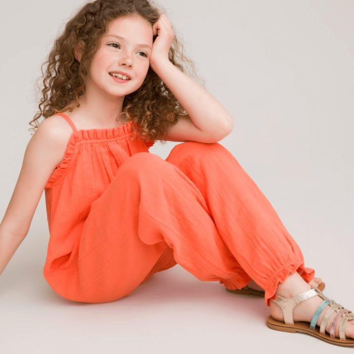 A young girl wearing a coral coloured jumpsuit.