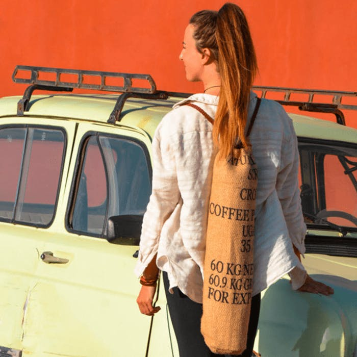 A woman next to a yellow car, carrying a yoga mat.