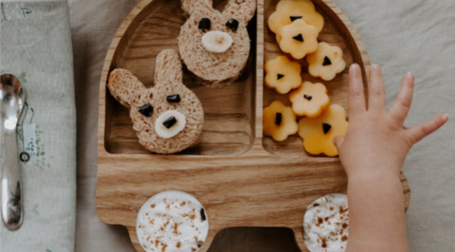 A babies hand reaching for snacks from a wooden plate.