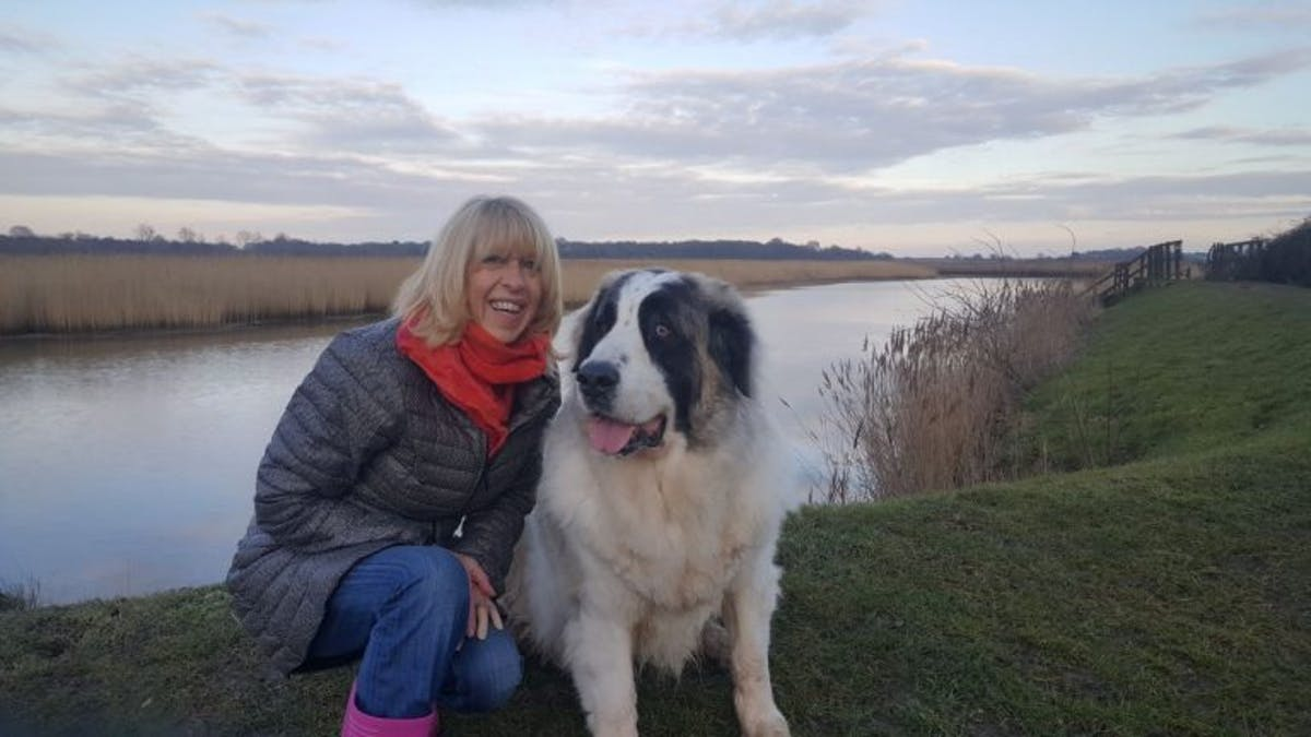 A woman and a dog posing for the camera by a riverside