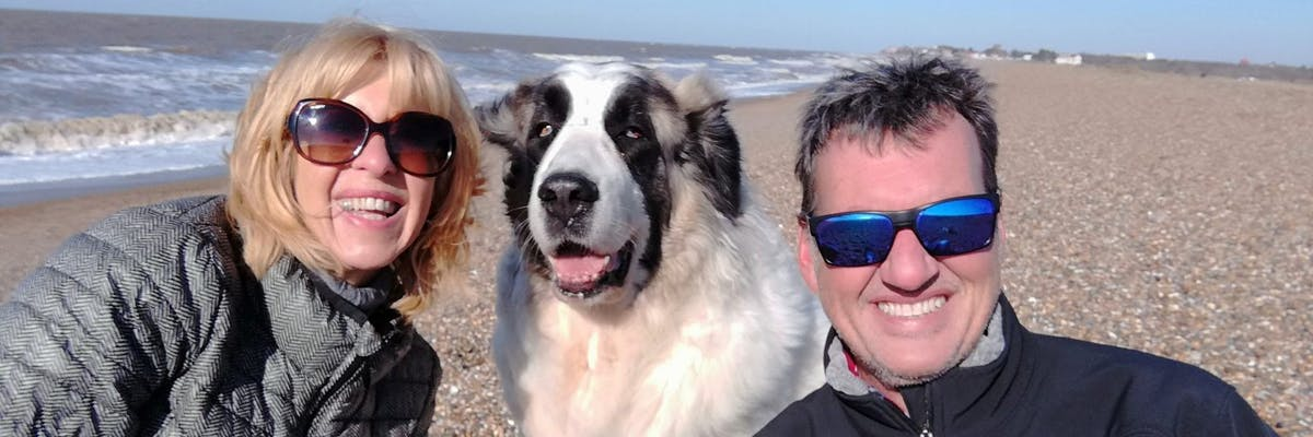 A woman, a man, and a dog smiling at the camera on the beach