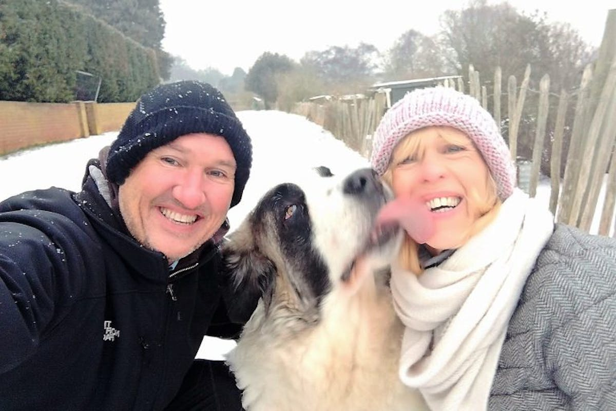 A man and a woman smiling at the camera, while a dog licks the woman's face