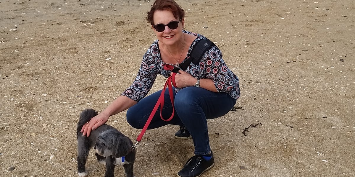 A woman on the beach smiling at the camera, petting a grey and white dog