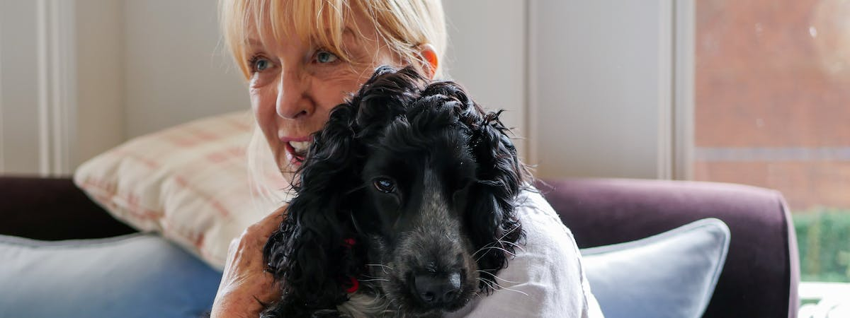A blonde woman holding a small black dog