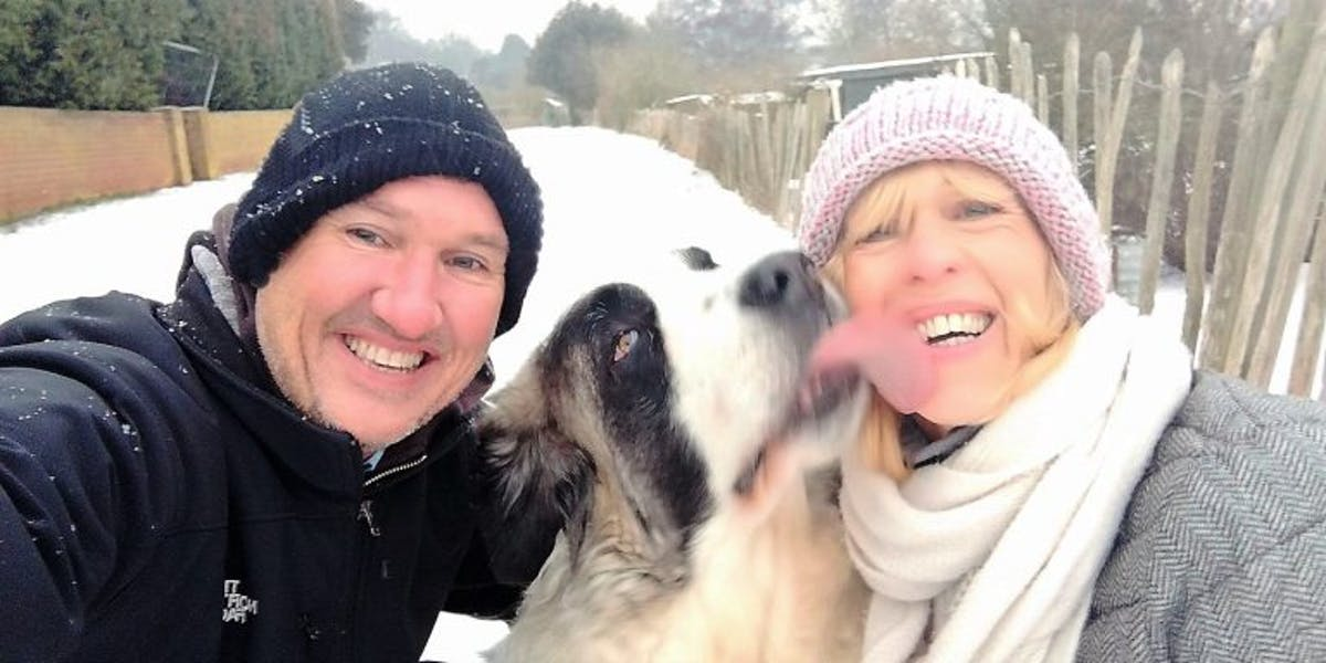 A man, a woman and a dog outside in the snow, the dog licking the woman's face
