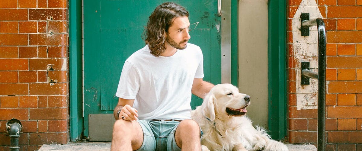 A man sitting on a step outside a doorway, stroking a Golden Retriever