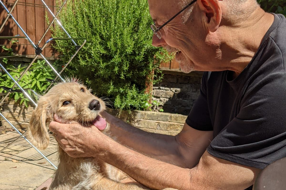 A man sitting outside in a garden holding the face of an excitable puppy