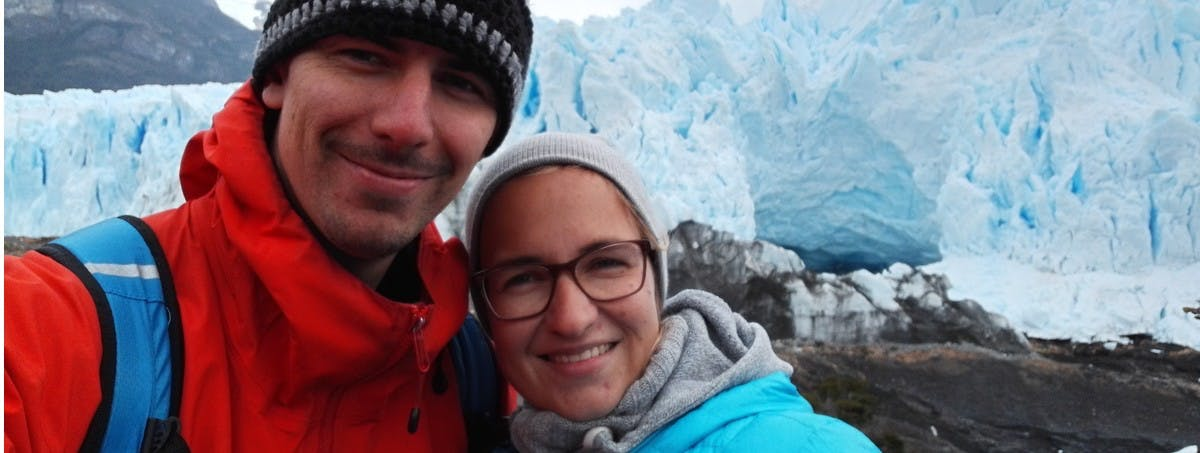 Couple standing infront of Iceberg on house sit