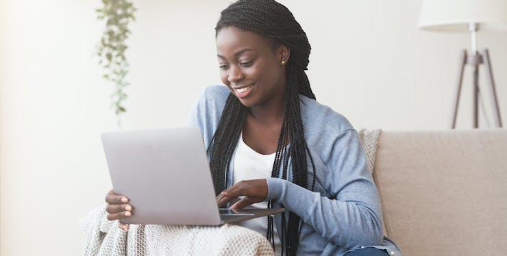 mulher sentada no sofá digitando no notebook