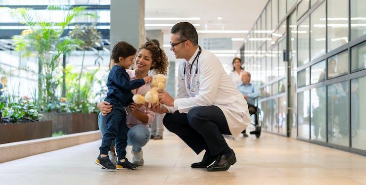 médico conversando com mãe e criança