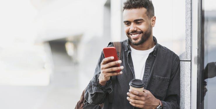 homem olhando o celular e segurando um copo de café